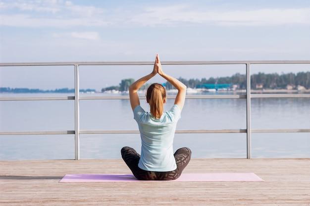 Junge frau macht yoga auf einer matte auf einem pier am meer und sitzt im lotussitz mit gefalteten händen nach oben