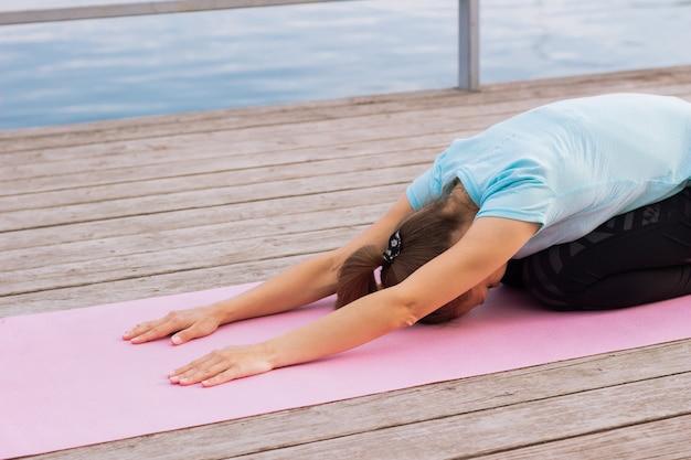 Junge frau macht yoga auf einer matte auf einem pier an einem see
