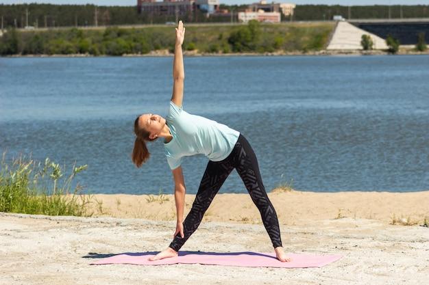 Junge frau macht yoga auf einer rosa matte am meer