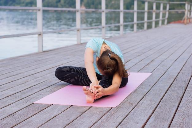 Junge frau macht yoga auf einer rosa matte auf einem pier am meer