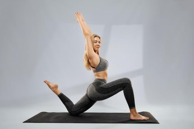 Junge frau macht yoga-krieger-pose auf gymnastikmatte