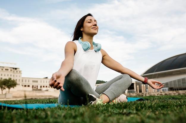 Junge frau macht yoga-sitzung im park