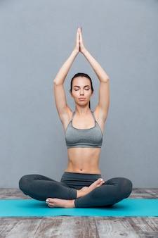 Junge frau macht yoga-übung padmasana (lotus pose) isoliert auf grauem hintergrund