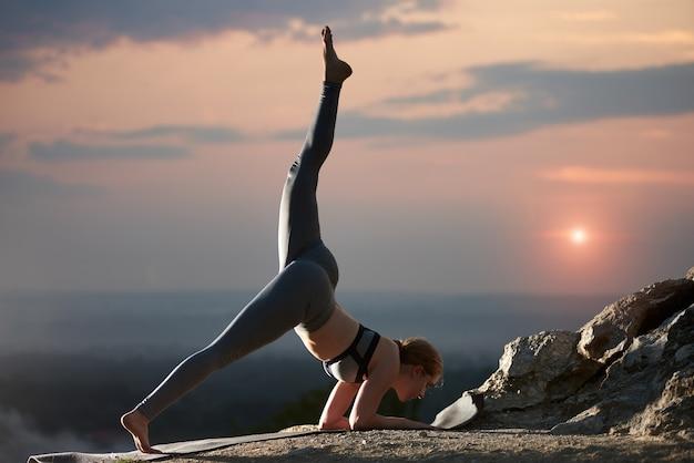 Junge frau macht yoga-übungen im freien bei sonnenuntergang