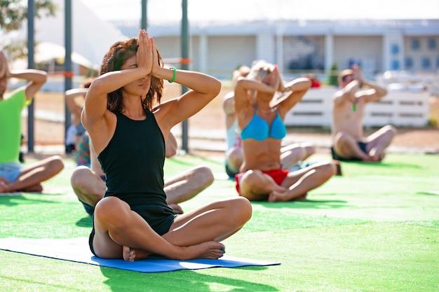 Junge frau macht yoga-übungen mit gruppe von altersgemischten menschen
