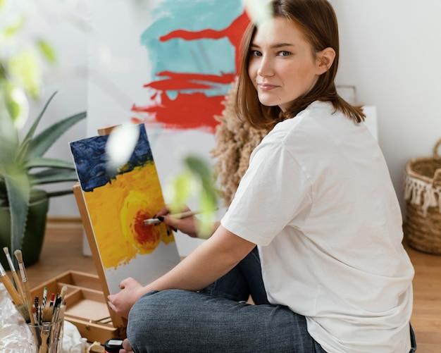 Junge frau malt mit acrylfarben zu hause