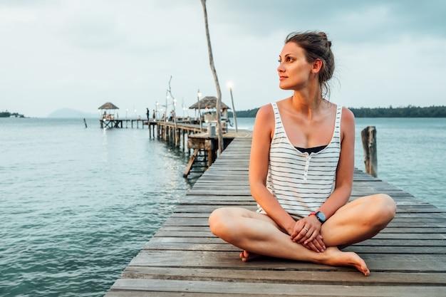 Junge frau meditiert am pier