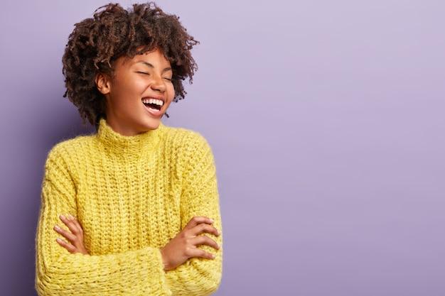 Junge frau mit afro-haarschnitt, der gelben pullover trägt