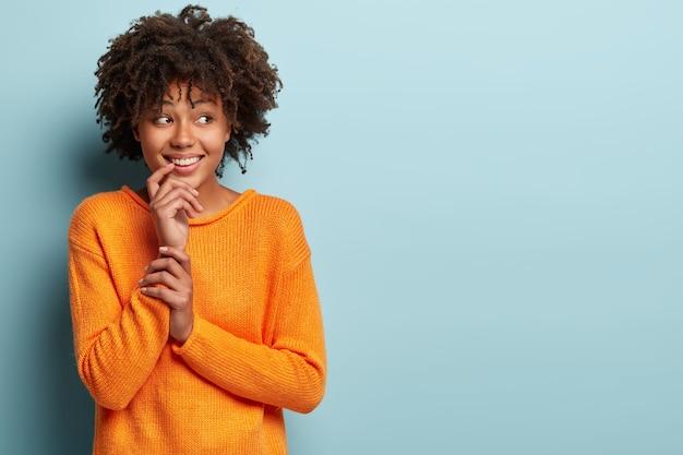 Junge frau mit afro-haarschnitt, der orange pullover trägt