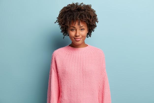 Junge frau mit afro-haarschnitt, der rosa pullover trägt