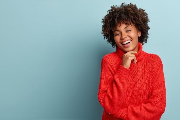 Junge frau mit afro-haarschnitt, die roten pullover trägt