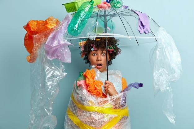 Junge frau mit afro-haarschnitt, die tasche mit plastikmüll hält
