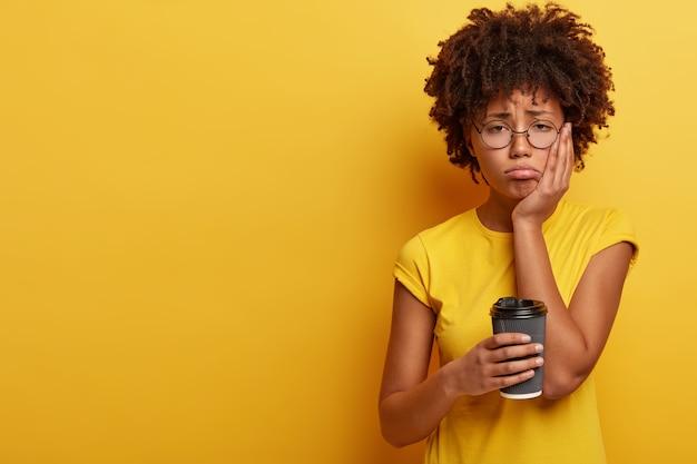 Junge frau mit afro-haarschnitt, die tasse kaffee hält