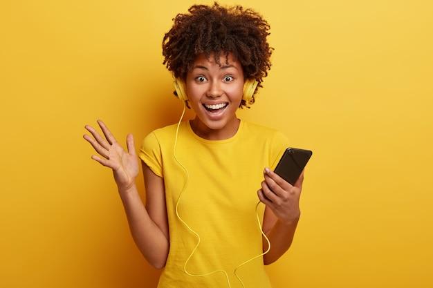 Junge frau mit afro-haarschnitt, gelbem t-shirt und kopfhörern
