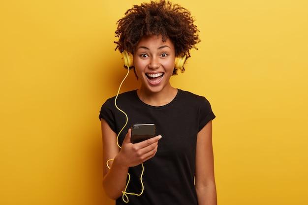 Junge frau mit afro-haarschnitt mit gelben kopfhörern