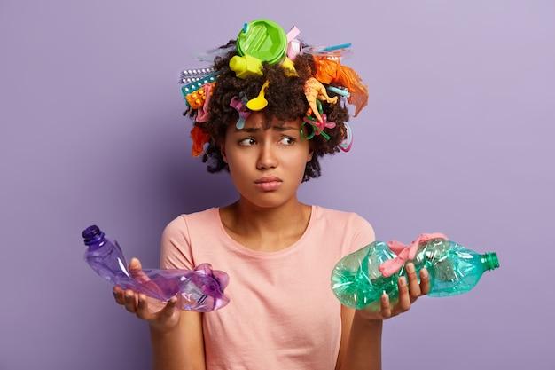 Junge frau mit afro-haarschnitt und plastikmüll im haar