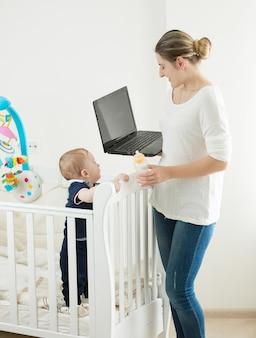 Junge frau mit baby, die zu hause am laptop arbeitet