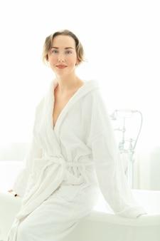 Junge frau mit bademantel nach der dusche