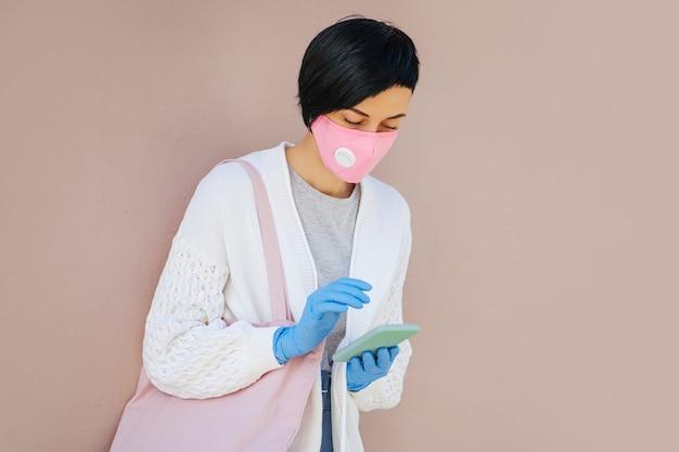 Junge frau mit baumwollmaske und medizinischen handschuhen, die während des ausbruchs von covid 19 smartphone auf der straße benutzt. schutz in der prävention des coronavirus. ein konzept der lieferung, online-service, app.