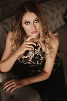 Junge frau mit blondem haar und perfektem trendigem make-up. schönes blondes modellmädchen mit modischem make-up, tiefblauen augen und verführerischem blick. konzept des modischen offiziellen make-ups und der glatten haut