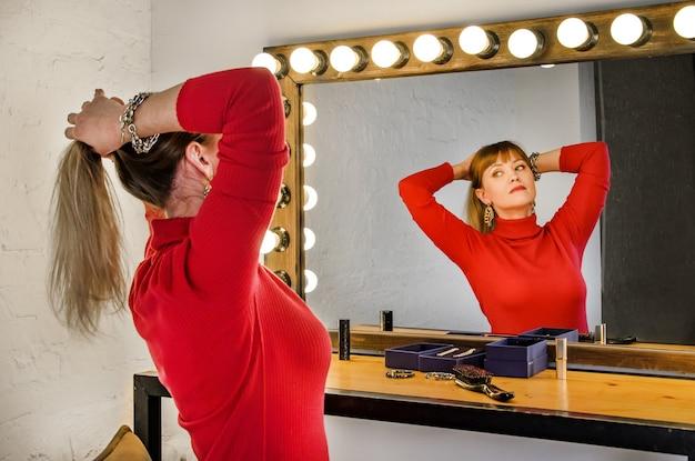Junge frau mit blonden haaren in rot auf schminktisch glättet ihre haare im spiegel