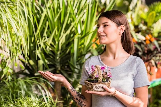 Junge frau mit blumen im korb, der an den grünpflanzen darstellt