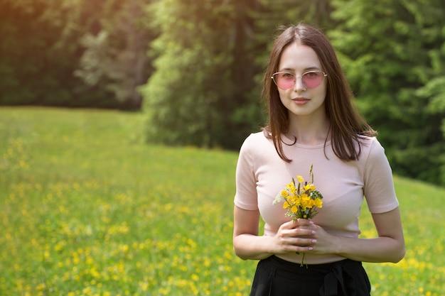 Junge frau mit blumenstrauß von wildflowers auf einem sonnigen rasen.