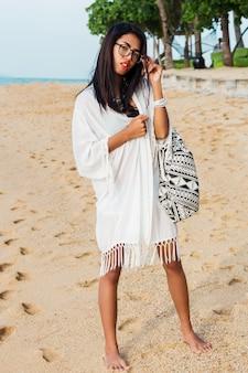 Junge frau mit boho-tasche, die am tropischen strand aufwirft