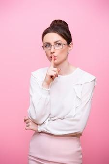 Junge frau mit brille hält einen zeigefinger in der nähe des mundes und fordert zum schweigen