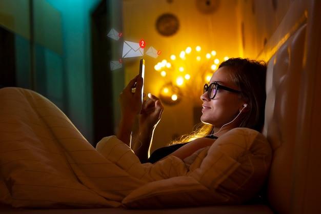 Junge frau mit brille in kopfhörern vor dem schlafengehen, die entspannende musik hört und mit geliebten menschen und freunden plaudert. chat nacht und surfen telefon. soziale netzwerke und telefonsucht.