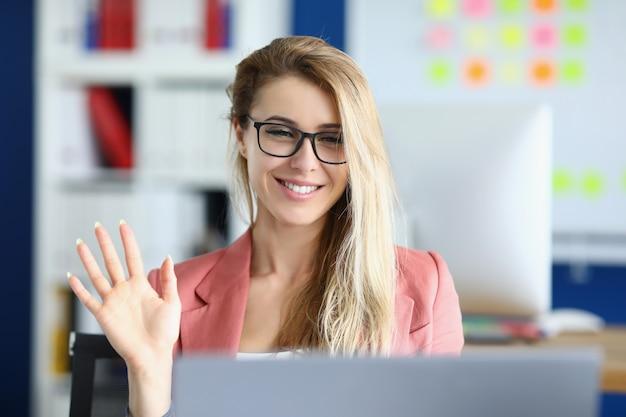 Junge frau mit brille winkt mit der hand am laptop-bildschirm im büro