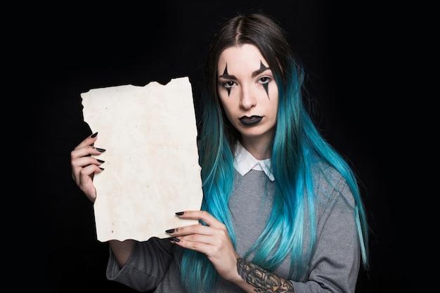 Junge frau mit dem blauen haar, das mit blatt papier aufwirft