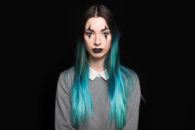 Junge frau mit dem blauen haar und make-up, die im studio stehen