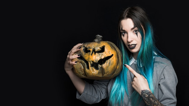 Junge frau mit dem blauen haar zeigend auf halloween-kürbis