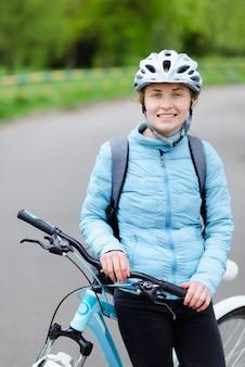 Junge frau mit dem fahrrad, das im park geht