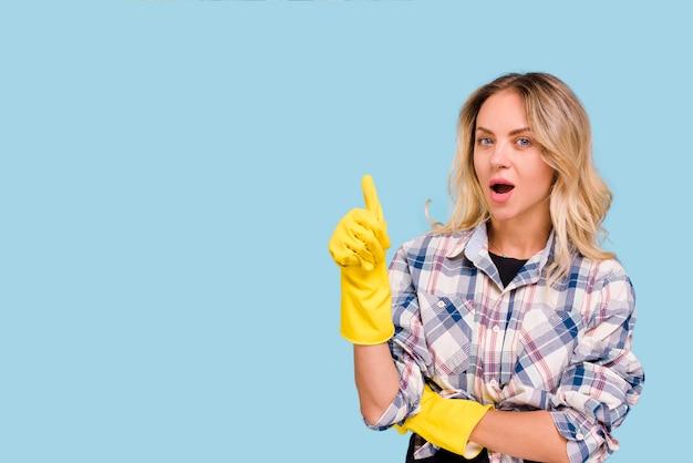 Junge frau mit dem gelben handschuh, der daumen herauf die geste betrachtet kamera zeigt