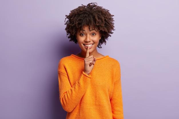 Junge frau mit dem gelockten haar, das orange pullover trägt