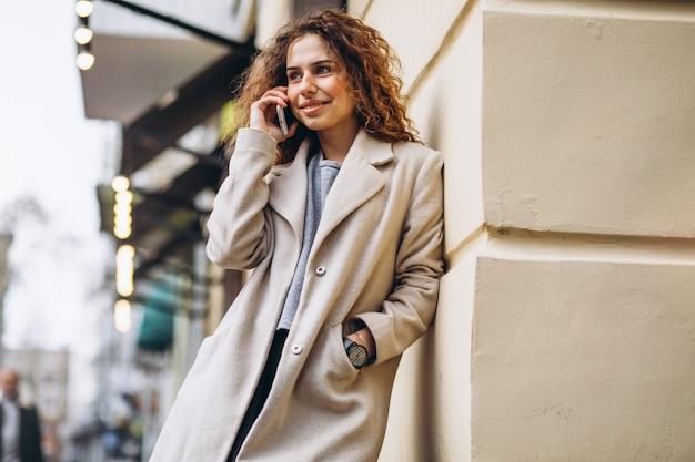 Junge frau mit dem gelockten haar unter verwendung des telefons an der straße