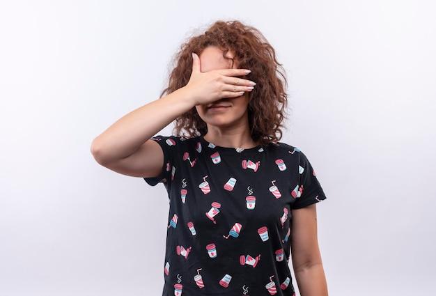Junge frau mit dem kurzen lockigen haar, das augen mit handlächeln bedeckt, die über weißer wand stehen