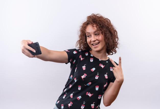 Junge frau mit dem kurzen lockigen haar, das selfie unter verwendung ihres smartphones nimmt, das zur kamera lächelt und siegeszeichen zeigt, das über weißer wand steht