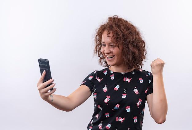 Junge frau mit dem kurzen lockigen haar, das smartphone hält geballte faust glücklich und aufgeregt freut sich über ihren erfolg, der über weißer wand steht