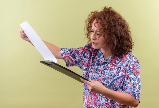 Junge frau mit dem kurzen lockigen haar im bunten hemd, das klemmbrett hält, das leere seiten mit ernstem gesicht betrachtet, das über grüner wand steht