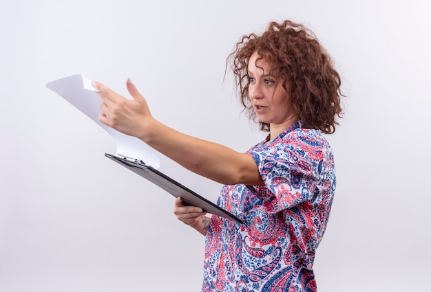 Junge frau mit dem kurzen lockigen haar im bunten hemd, das zwischenablage hält, die leere seiten mit ernstem gesicht betrachtet, das über weißer wand steht