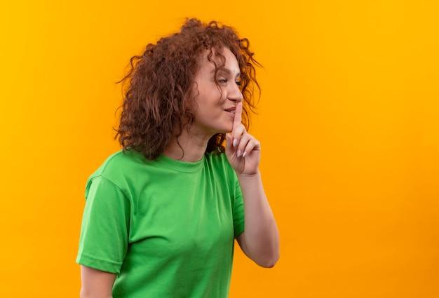 Junge frau mit dem kurzen lockigen haar im grünen t-shirt, das beiseite schaut, das stille geste mit finger auf den lippen stehend macht