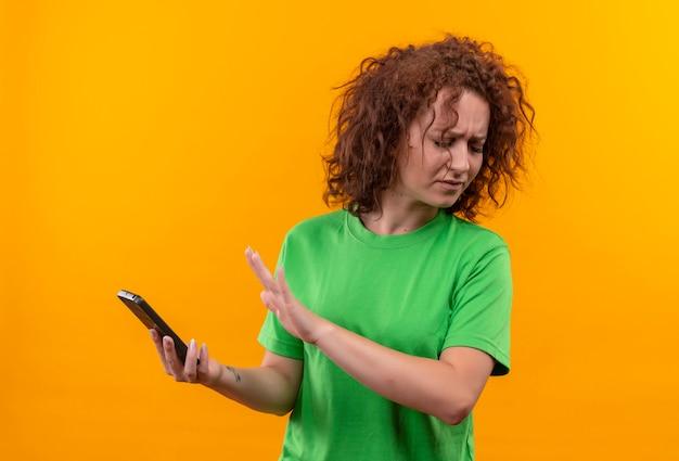 Junge frau mit dem kurzen lockigen haar im grünen t-shirt, das smartphone hält, das verteidigungsgeste mit der anderen hand gegen ihr handy macht, das unzufrieden steht stehend