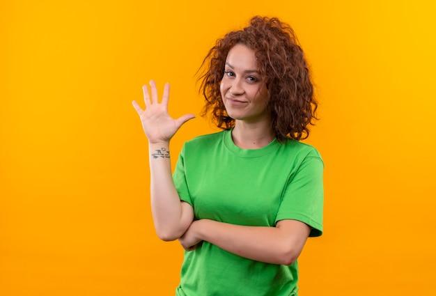Junge frau mit dem kurzen lockigen haar im grünen t-shirt lächelnd winkend mit der hand, die über orange wand steht