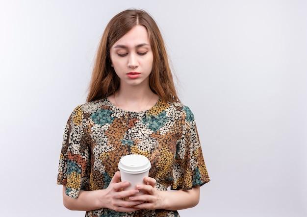 Junge frau mit dem langen haar, das buntes kleid trägt, das kaffeekappe sehr hält und es mit traurigem ausdruck auf gesicht betrachtet, das über weißer wand steht