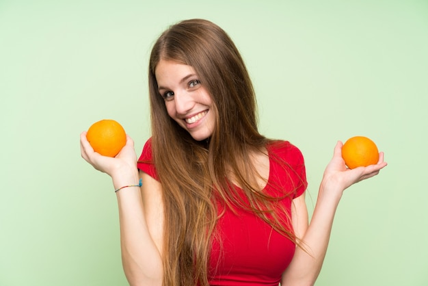 Junge frau mit dem langen haar, das eine orange anhält