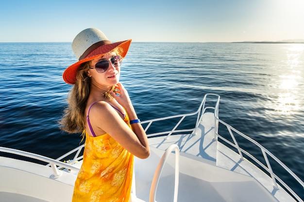 Junge frau mit dem langen haar, das gelbes kleid und strohhut trägt, die auf weißem yachtdeck stehen und blick auf blaues meerwasser genießen.