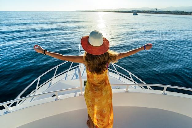 Junge frau mit dem langen haar, das gelbes kleid und strohhut trägt, die mit erhöhten händen auf weißem yachtdeck stehen und blick auf blaues meerwasser genießen.